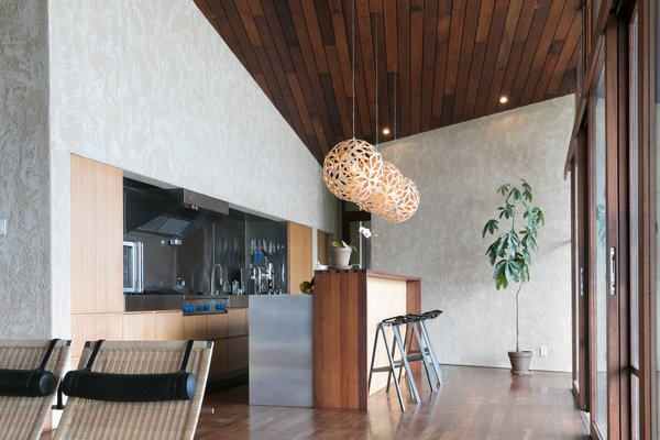 Modern home with kitchen, wood cabinet, metal counter, dark hardwood floor, metal backsplashe, pendant lighting, and refrigerator. Photo 7 of The Clifftop House