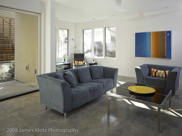 Modern home with bench, medium hardwood floor, lamps, front yard, table, office, and trees. Photo 3 of East Residence