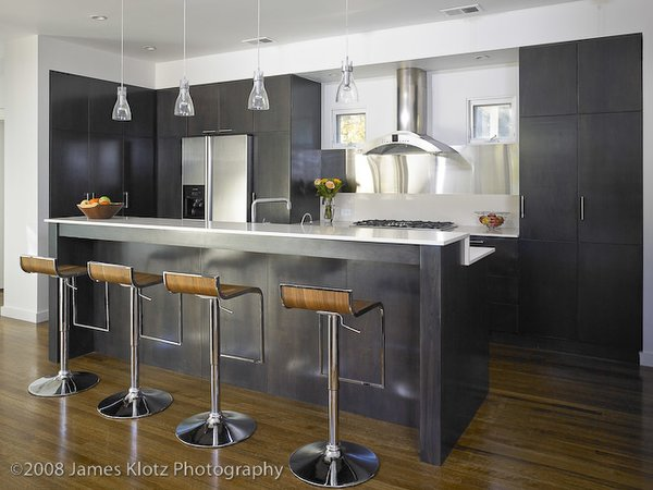Modern home with bench, front yard, table, lamps, medium hardwood floor, trees, and kitchen. Photo 4 of East Residence