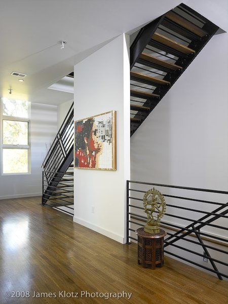 Modern home with bench, front yard, table, lamps, medium hardwood floor, hallway, and trees. Photo 5 of East Residence
