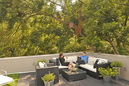 Modern home with bench, table, lamps, medium hardwood floor, trees, bed, night stands, outdoor, and front yard. Photo 13 of East Residence