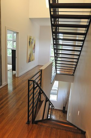 Modern home with bench, table, front yard, lamps, medium hardwood floor, bed, night stands, hallway, and trees. Photo 14 of East Residence
