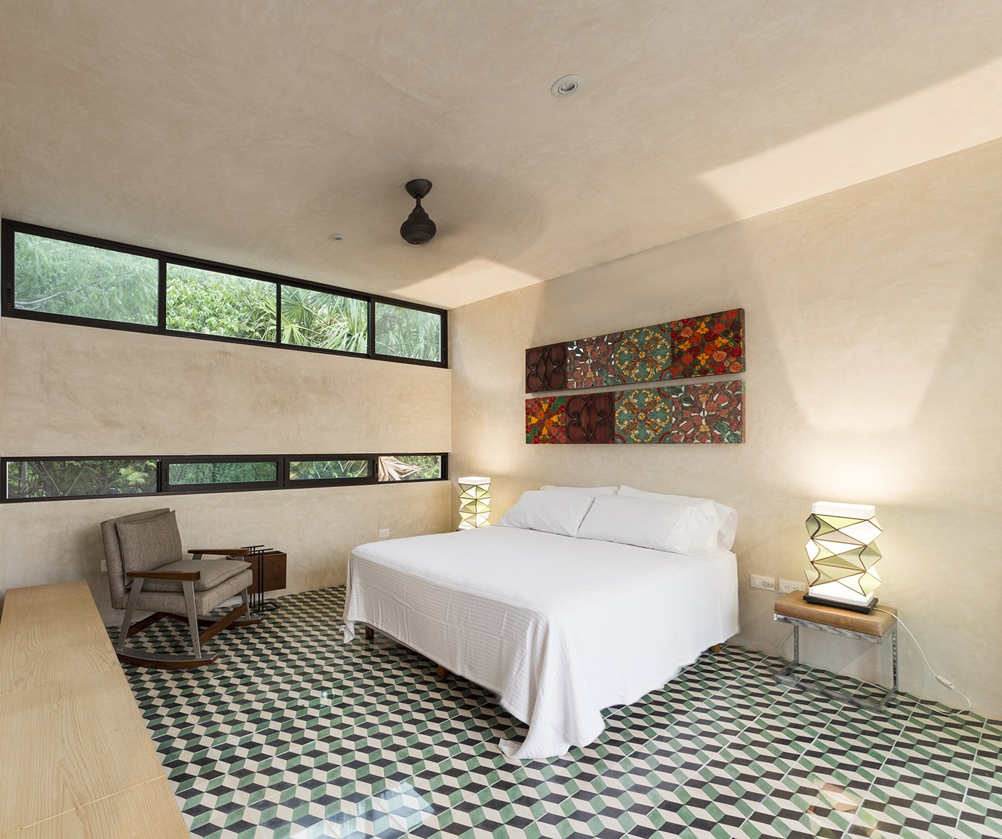 Upstairs bedroom take advantage of the natural surounding from the neighborhood Tagged: Bedroom, Bed, Table Lighting, Cement Tile Floor, Chair, and Bench.  Lemon Tree House by Taller Estilo Arquitectura S de R.L de C.V