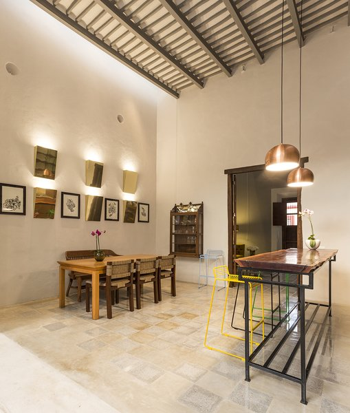 Modern home with dining room, wall lighting, pendant lighting, chair, table, shelves, and cement tile floor. The old ceilings and walls of the existing structure  were preserved to keep the spirit of the old house Photo 6 of Lemon Tree House