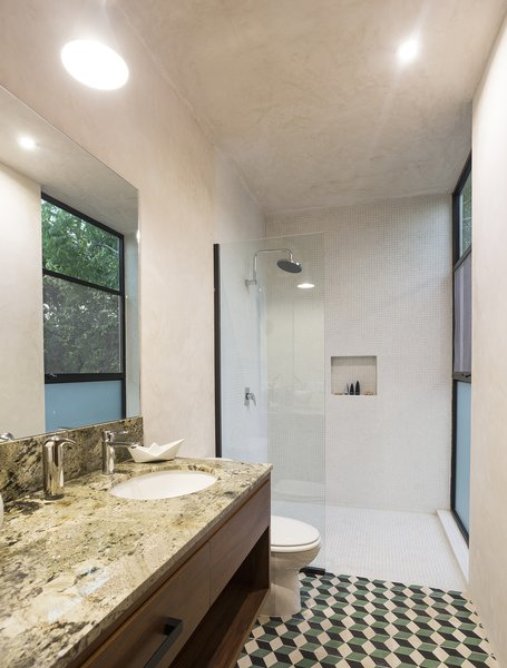 Modern home with bath room, marble counter, open shower, cement tile floor, undermount sink, pendant lighting, concrete wall, and one piece toilet. White polished concrete walls contrast with the colorfull Cement Tiles and the Marble on counter Photo 2 of Lemon Tree House