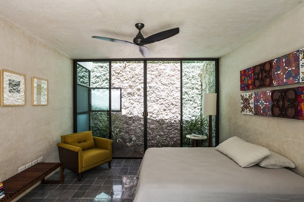 Modern home with bedroom, chair, cement tile floor, lamps, and bed. A Light well provide natural light and ventilation to the downstairs bedroom Photo 3 of Lemon Tree House