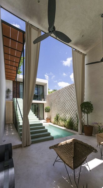 Modern home with outdoor, concrete patio, porch, deck, trees, horizontal fence, and plunge pool. The two areas of the house get conected trough the stairs volume and the light cover for the passway Photo 5 of Lemon Tree House