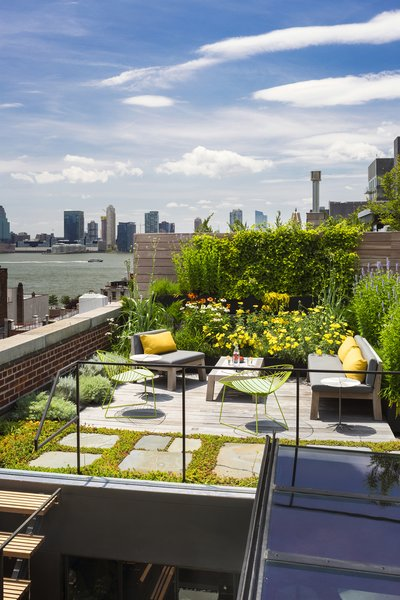 The new wooden rooftop terrace is surrounded by a green roof garden utilizing reclaimed bluestone pavers and native plant species that require little water while insulating the environment below. Photo 5 of Tribeca Loft modern home