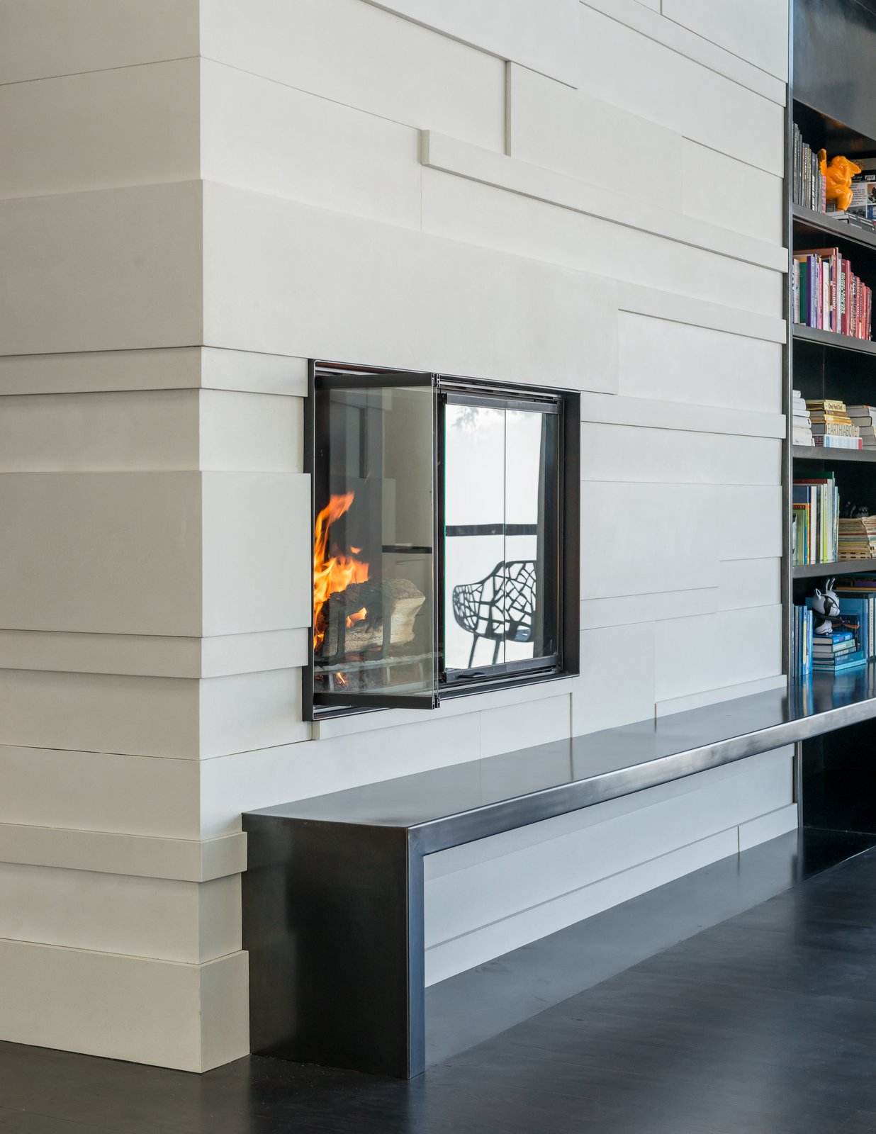 Custom concrete tiles and a steel hearth complete the fireplace surround.
