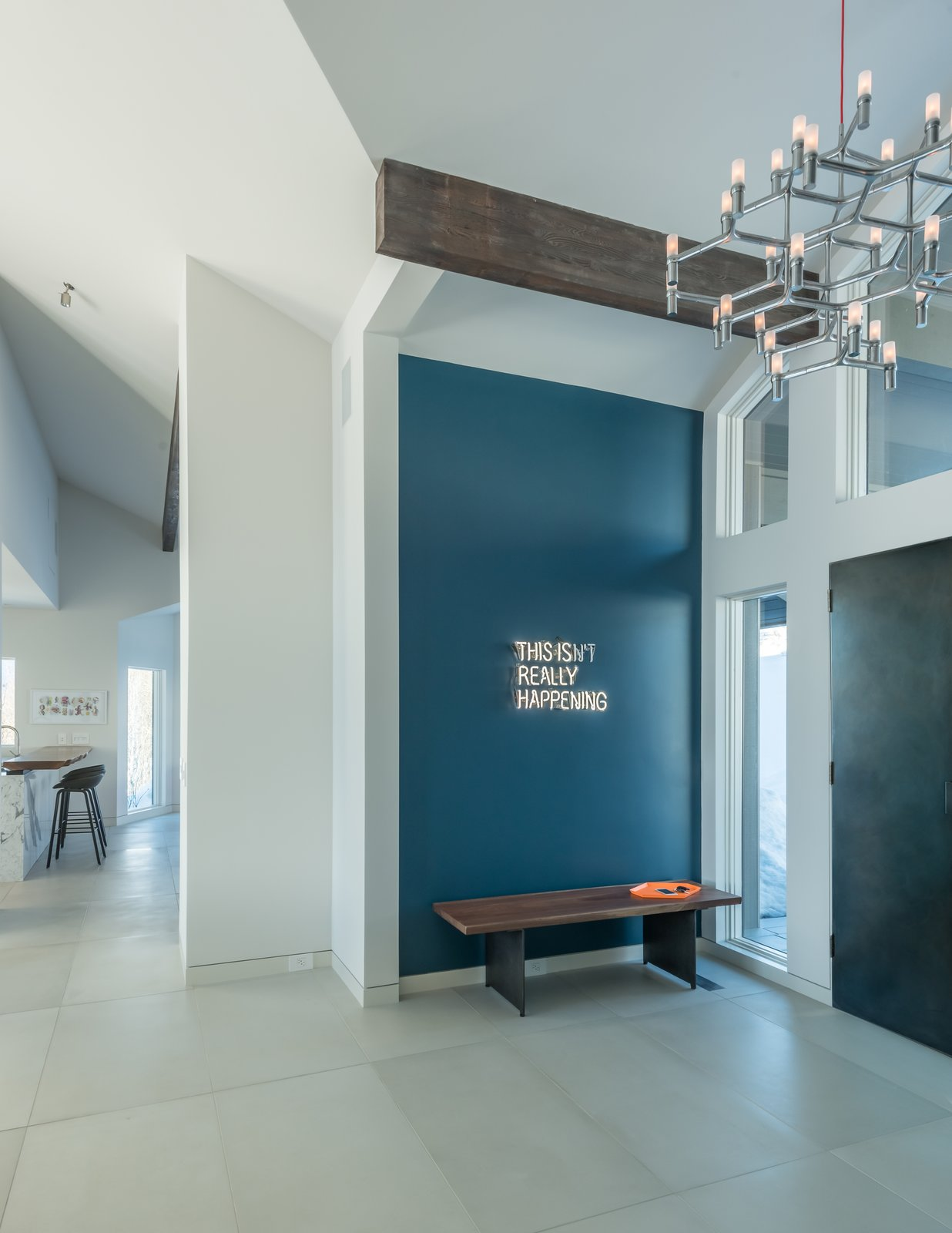 A playful neon wall installation greets guests.  Crown Major Suspension pendant and entry doors clad in steel set the tone for the interior spaces.  San Francisco Meets Jackson Hole in a Modern Renovation by Carney Logan Burke Architects