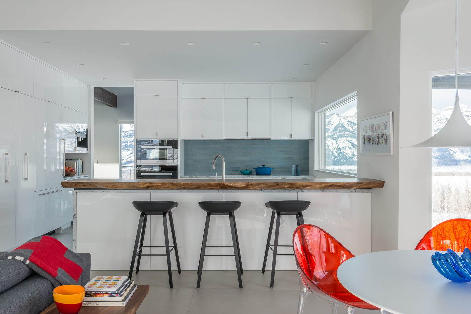 Kitchen cabinets are painted white and lacquered with an automotive finish.  Heath Tile adds color in the backsplash while a live-edge walnut counter adds depth to the room. San Francisco Meets Jackson Hole in a Modern Renovation by Carney Logan Burke Architects