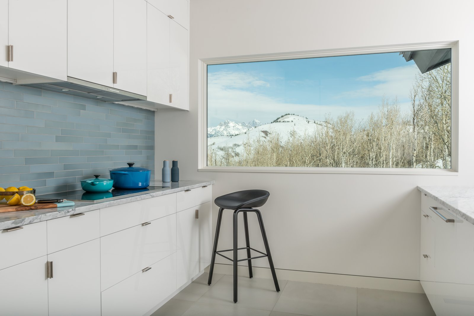 Honed, white Carrera marble countertops blend with exterior views to the Teton Mountain Range.  San Francisco Meets Jackson Hole in a Modern Renovation by Carney Logan Burke Architects