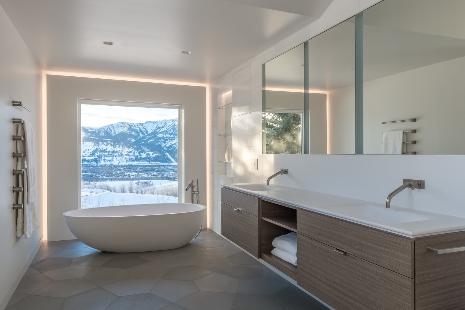 Previous master bathroom was divided into three separate spaces, with the mountain view terminating in a closet.  The walls were removed to open views to the west and create one large space.  Custom pentagon shaped concrete tiles compliment the Eco-Wood veneer floating vanity.