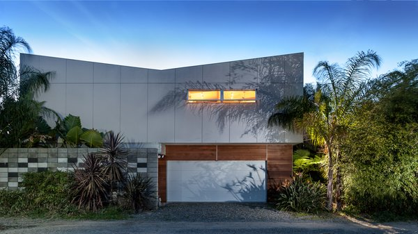 Modern home with outdoor, side yard, horizontal fence, landscape lighting, trees, shrubs, and flowers. Alley Elevation Photo  of Land Park Residence