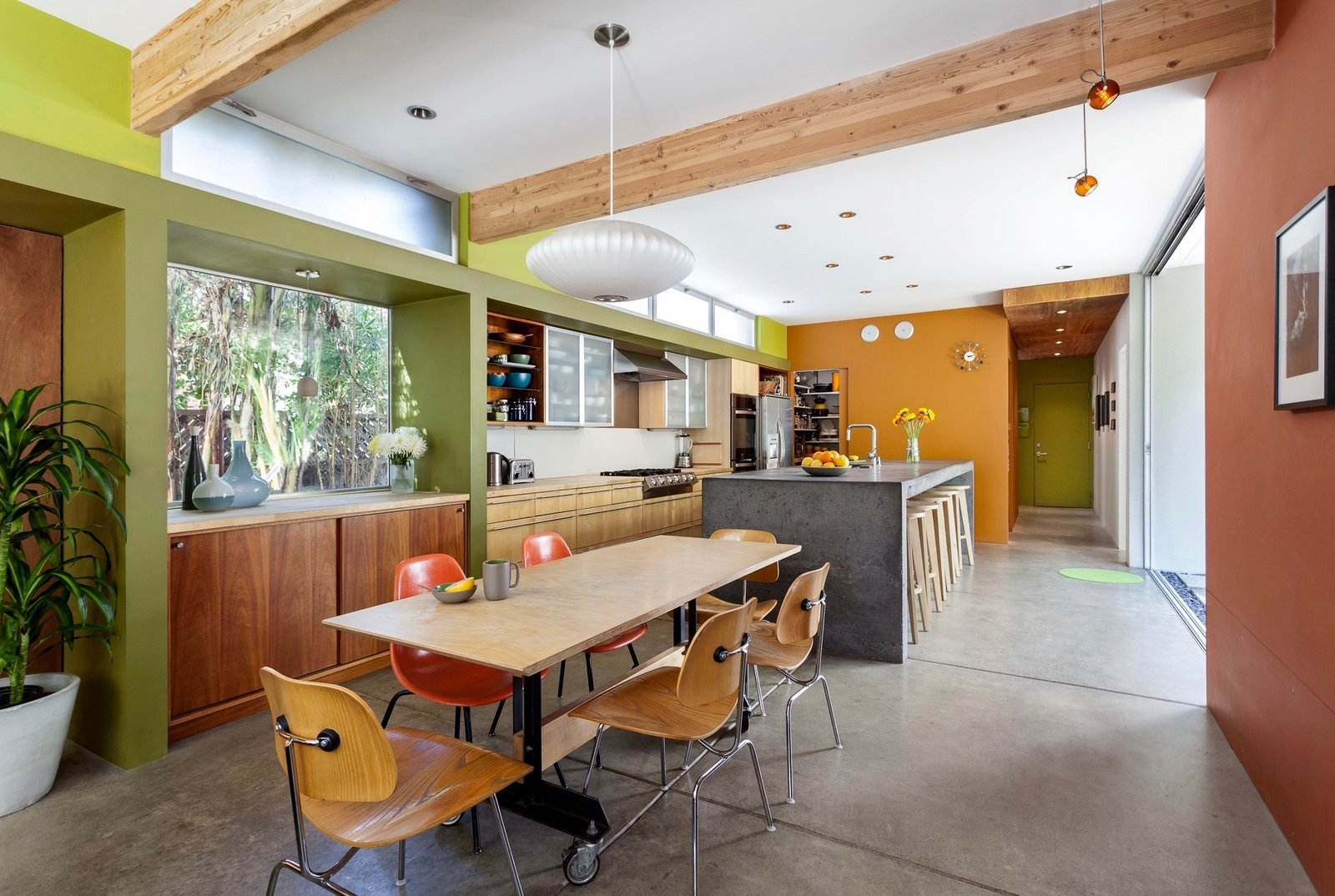 Dining Room to Kitchen Tagged: Concrete Counter, Dining Room, Table, Bar, Stools, Accent Lighting, Chair, Storage, Pendant Lighting, Recessed Lighting, and Concrete Floor.  Land Park Residence by serrao design | Architecture