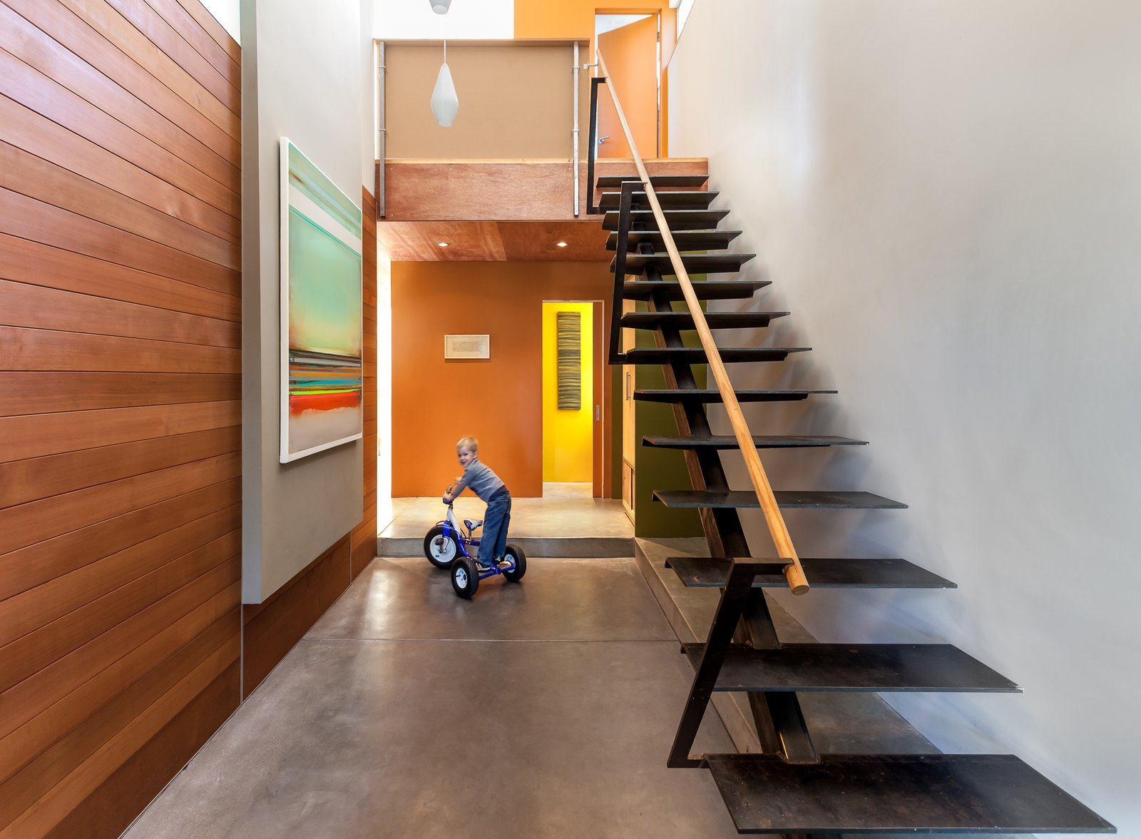 Entry and stairs Tagged: Concrete Counter, Wood Cabinet, Metal Cabinet, Concrete Backsplashe, Refrigerator, Wall Oven, Cooktops, Range Hood, Dishwasher, Undermount Sink, Bed, Chair, Track Lighting, Storage, Ceiling Lighting, Medium Hardwood Floor, Back Yard, Walkways, Trees, and Shrubs.  Land Park Residence by serrao design | Architecture