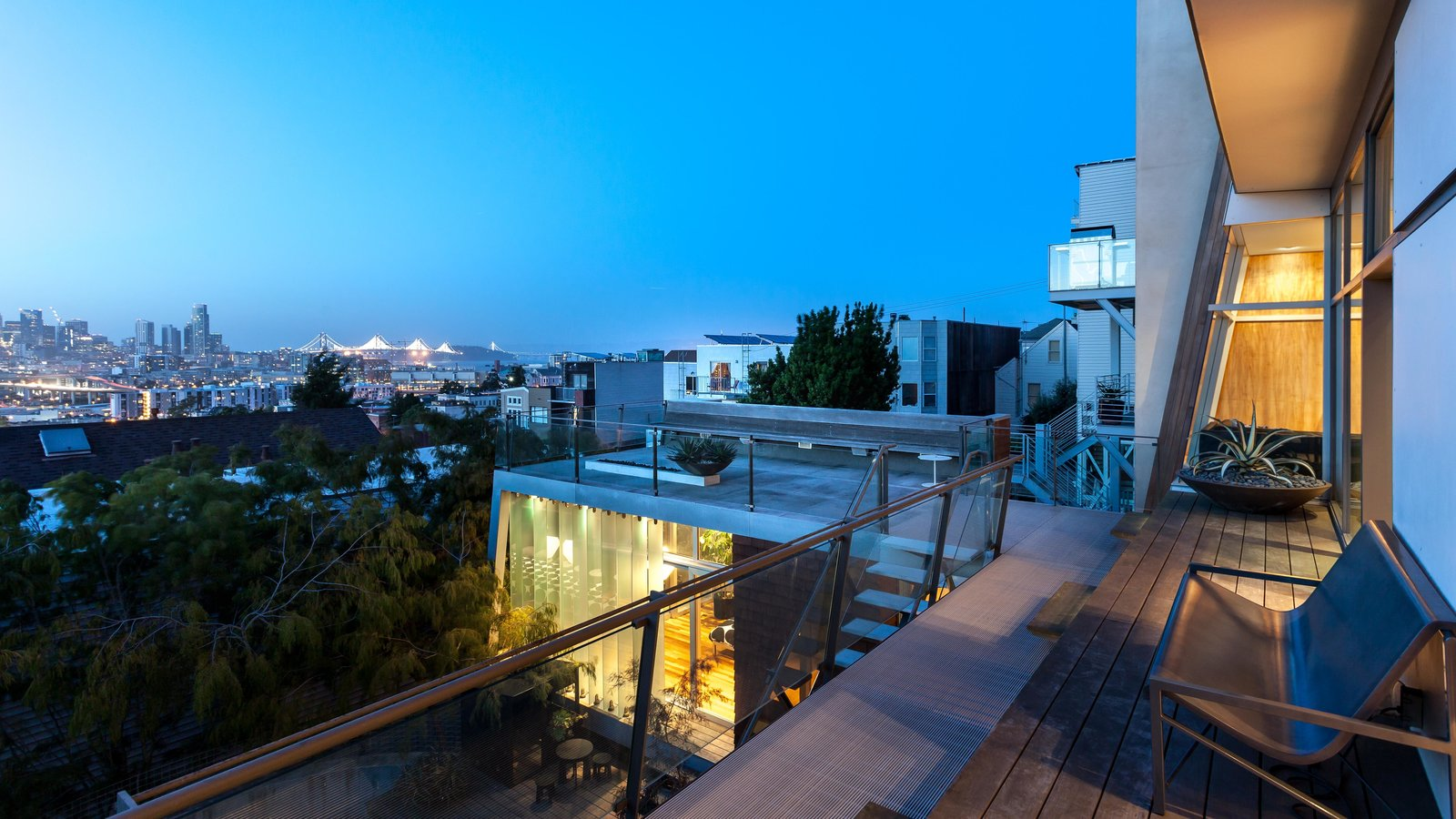 The evening view of the glass louvered studio below with the roof deck.