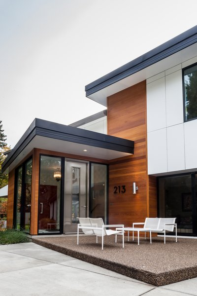 While maintaining the existing house structure, an entirely new, modern home was created from new interiors placed on to a new exterior skin. The entire exterior was revised with new cladding, metal roof, insulation, and windows. An addition opened the space to embrace higher ceilings and to introduce varying floor levels in order to create a fresh, dynamic flow within the home. The re-cladding of the house allowed for a complete change in the home's style while also completing significant thermal improvements. Photo  of Creek Drive Residence modern home
