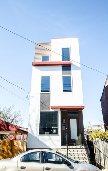 The row house façade takes a playful tone, with a mix of exterior cladding materials and horizontal red projections dividing up the three stories and making the narrow parcel stand out. Photo 3 of Charlotte Street Residence modern home