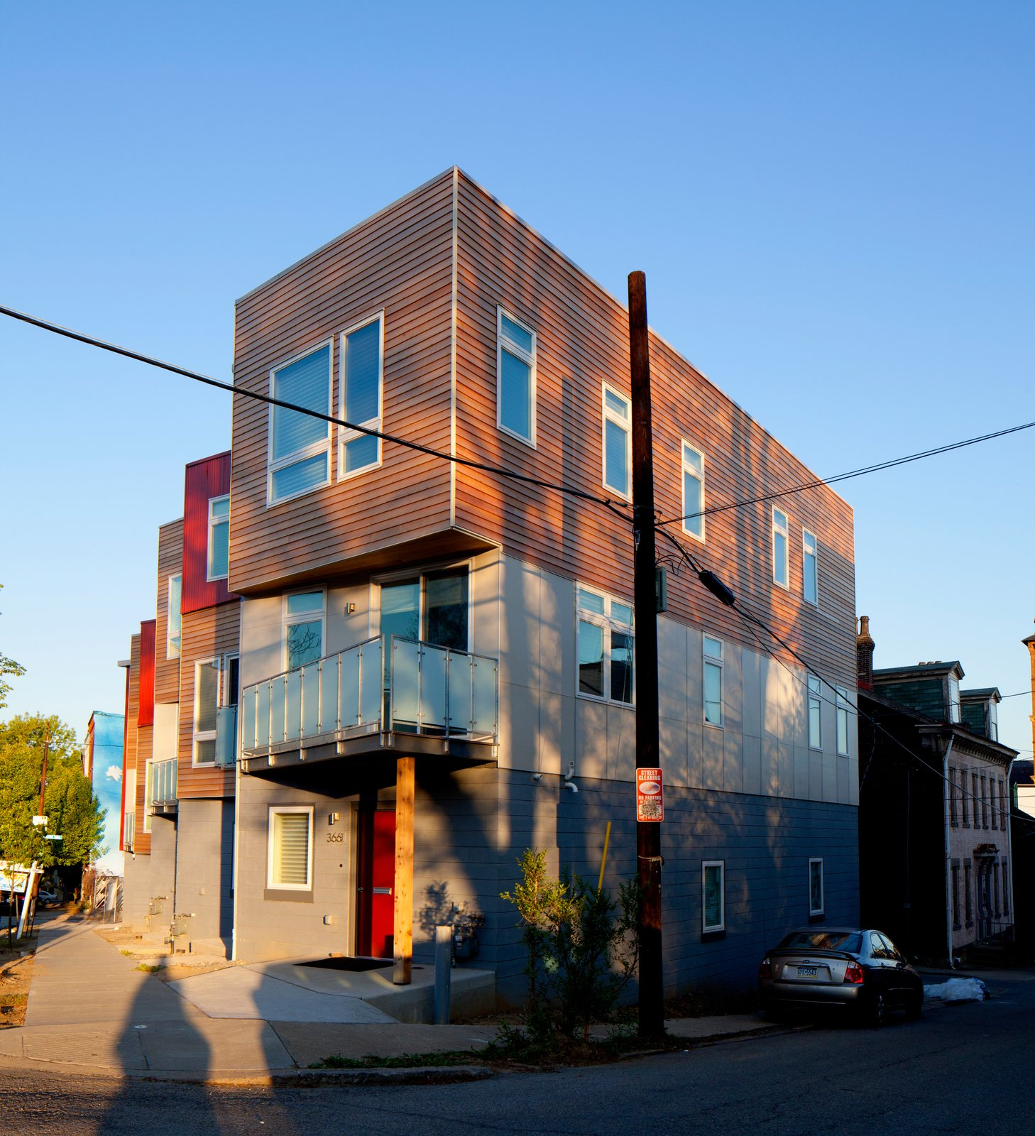 The Croghan's Edge Townhouse project addressed a difficult infill challenge in Pittsburgh's dense urban Lawrenceville neighborhood. The challenge was to accommodate four distinct for-sale residences on a small triangular site of only 3,300 square feet in an area that is surrounded by two streets and an alley. Additionally, the developer's intent and desire was to use factory-built modular components for the upper stories. The solution was to develop a scheme that not only addressed the neighborhood row house scale, but also provided a contemporary interpretation of the neighborhood context. Our design turned the site problems into opportunities for a unique solution.  Croghan's Edge Townhomes by mossArchitects