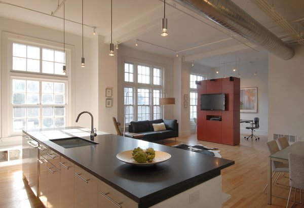"""Punctuating the white palette and historic building details as pops of modern design and color are two freestanding volumes, clad in custom red panels and placed so as to define specific living spaces within the long, rectangular loft. These """"cubes"""" separate public zones from private and create rooms without walls or doors, while appearing to float under the 12-foot-high ceilings. Photo 2 of Y Lofts modern home"""