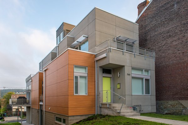 The massing of the Ligonier Street Residence largely consists of a narrow, articulated rectangular volume that is bisected by a custom central staircase that links all four levels of the 3,557 square foot home. The natural sloping topography of the site allows for access to the home at the lower basement level from an alley condition at the downhill property edge and at the first floor from the public street at the uphill property edge. Photo  of Ligonier Street Residence modern home