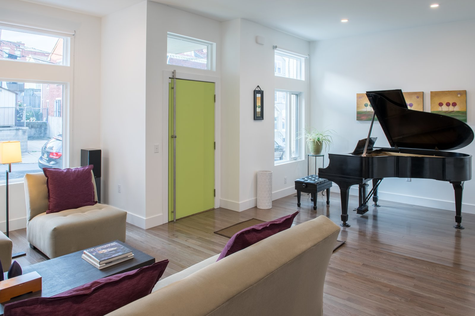 The first floor features a public entry from the street, leading to a formal living room with an alcove for the couple's baby grand piano.  Ligonier Street Residence by mossArchitects