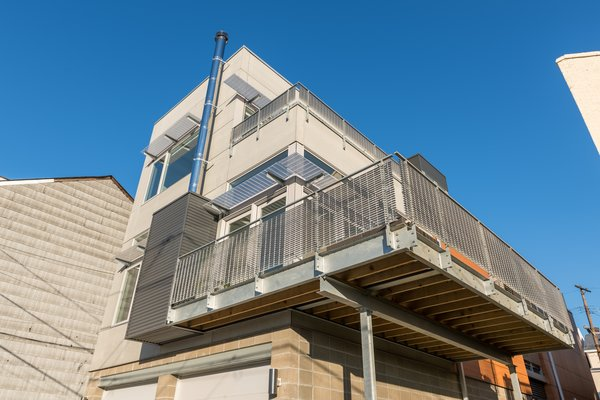 Custom designed galvanized steel and aluminum bar grating sunshades add a layer of detail and articulation to the exterior design, while eliminating glare and heat gain from direct sunlight to interior spaces. Photo 5 of Ligonier Street Residence modern home