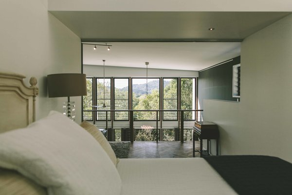 The bedroom captures the view over the void of the living space and out into the treetops. Photo 8 of Eco 234 modern home