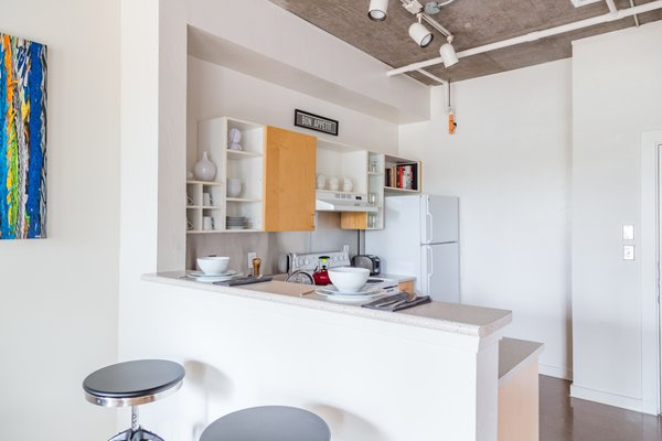 The dining area was outfitted with industrial style barstools as a nod to the loft's raw elements and features. Photo 7 of Witt Place Loft modern home