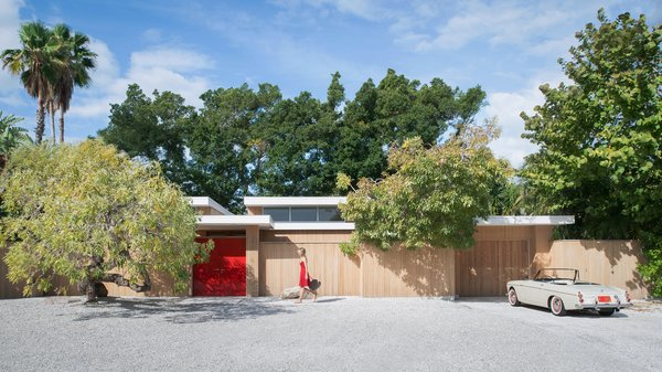 The Pavilion House's outer wall encircles a snaking courtyard that connects many of the home's interior spaces. After a step inside the lipstick red door, guests are greeted with an entrance into the home's exterior or to private patio on the left. Within that outer wall, both indoor and outdoor spaces appear to be one in the same. Photo  of The Pavilion House modern home
