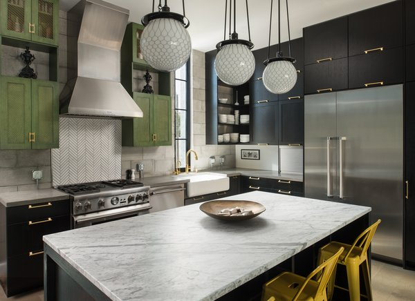 The kitchen is the heart of the home, and its design was carefully appointed with craftwork by local artisans. Brass pulls were custom designed and crafted to suit the space. The metal mesh on the upper cabinets was replicated with milled details in the cabinets beneath them. Concrete and marble counter tops provided a solid balance of industrial design and luxury.