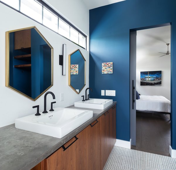 Modern home with bath room, concrete counter, wall lighting, and ceramic tile floor. Bold colors, geometric design elements and warm woods give grand appeal to the home's private spaces. Here, the master bathroom is bright and bold, but relaxed and functional. Photo 12 of 400SOLA