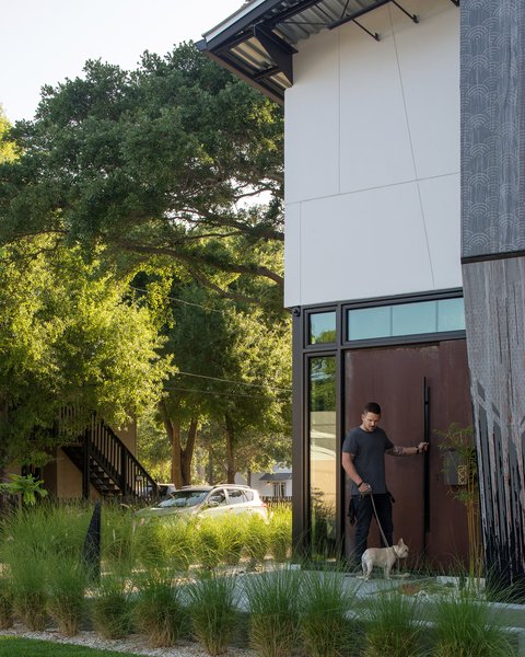 Modern home with outdoor, front yard, grass, shrubs, and trees. Each detail in the home was treated as an opportunity for expression. Here, a tall, weathered-steel door pivots smoothly with a tug on its leather-bound handle.  Photo 2 of 400SOLA