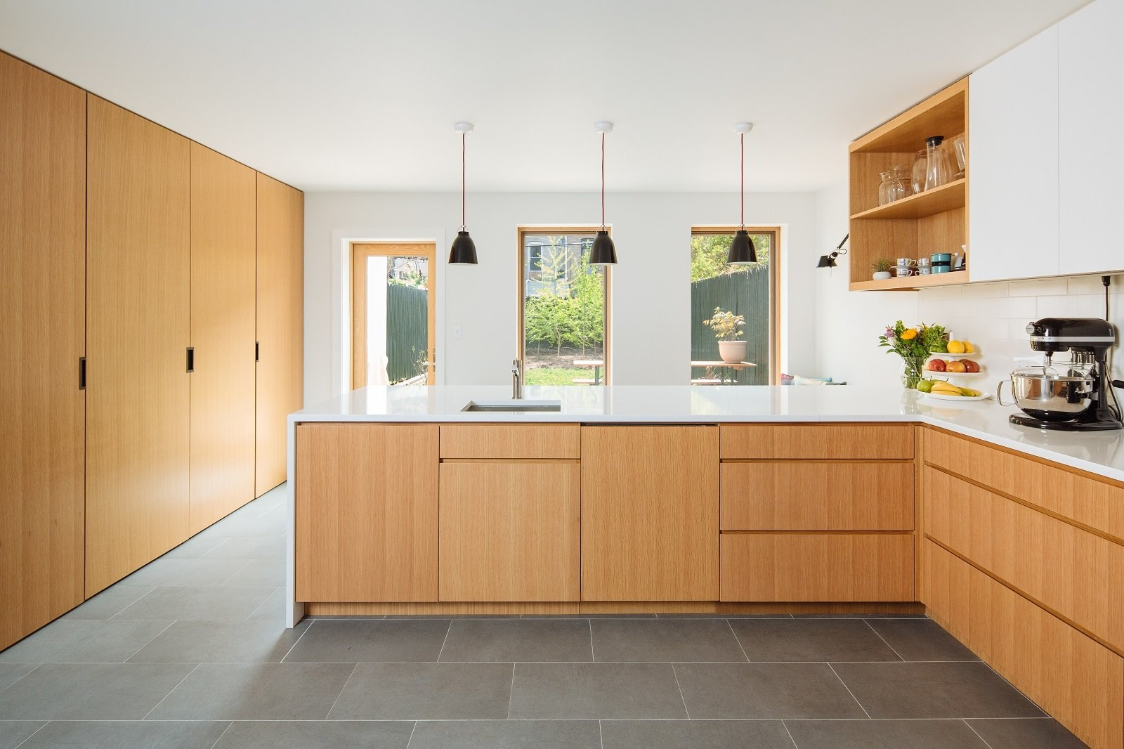 Custom white oak cabinetry provides a clean interior  Tagged: Kitchen, White Cabinet, Engineered Quartz Counter, Wood Cabinet, Subway Tile Backsplashe, Pendant Lighting, Porcelain Tile Floor, Accent Lighting, Dishwasher, and Undermount Sink.  Brooklyn Brownstone by Sonya Lee Architect llc