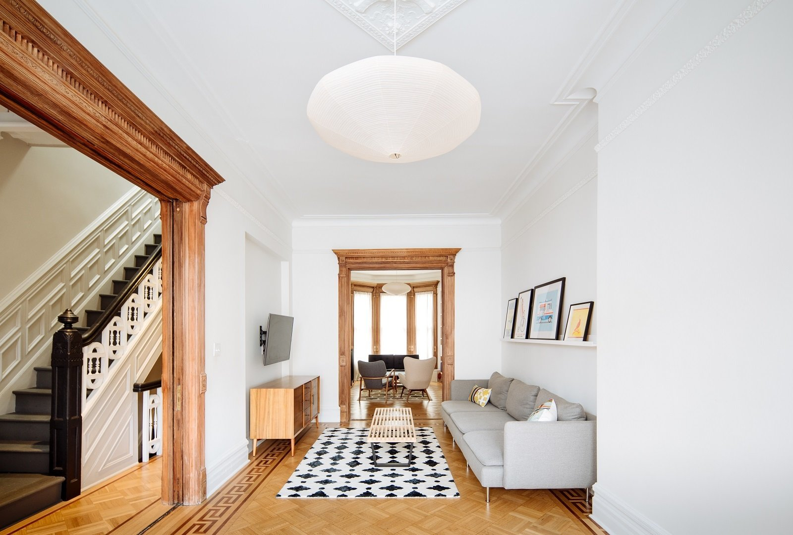 Parlour level Living Room: restored existing woodwork  bringing it back to life Tagged: Living Room, Sofa, Pendant Lighting, Console Tables, Medium Hardwood Floor, Light Hardwood Floor, and Accent Lighting.  Brooklyn Brownstone by Sonya Lee Architect llc