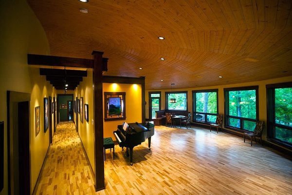 Modern home with recessed lighting, light hardwood floor, windows, and casement window type. This home takes advantage of the panoramic views with expansive windows Photo 2 of A Deltec Tree House