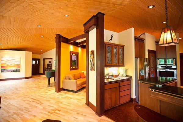 Modern home with kitchen, granite counter, wood cabinet, ceiling lighting, light hardwood floor, recessed lighting, refrigerator, and wall oven. The kitchen and seating area Photo 8 of A Deltec Tree House
