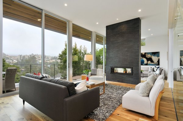 Modern home with living room, two-sided fireplace, and sofa. Photo 6 of Acacia Residence