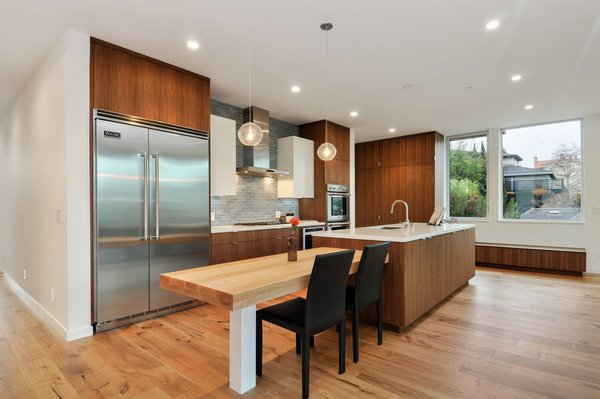 Modern home with kitchen, refrigerator, pendant lighting, subway tile backsplashe, and wood cabinet. Photo 11 of Acacia Residence