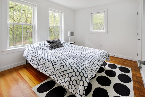Modern home with bedroom, bed, night stands, table lighting, and medium hardwood floor. Photo 6 of The Bracy House