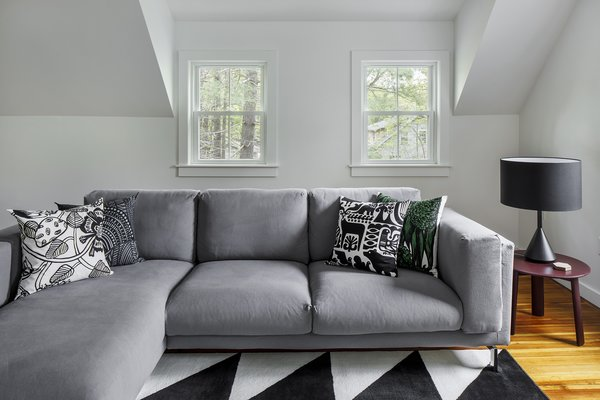 Modern home with sofa, medium hardwood floor, end tables, windows, table lighting, vinyl, and double hung window type. Photo 7 of The Bracy House