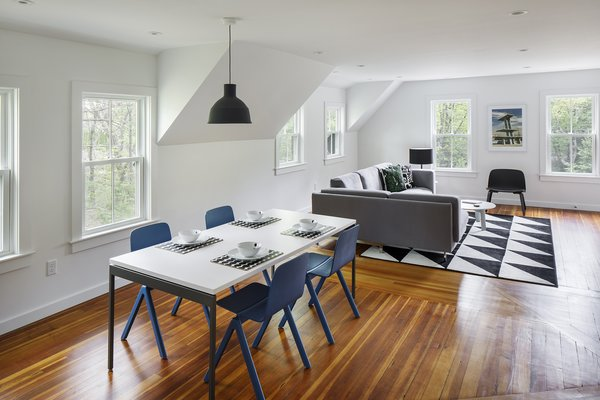 Modern home with chair, table, recessed lighting, ceiling lighting, medium hardwood floor, double hung window type, vinyl, dining room, and pendant lighting. Photo 8 of The Bracy House