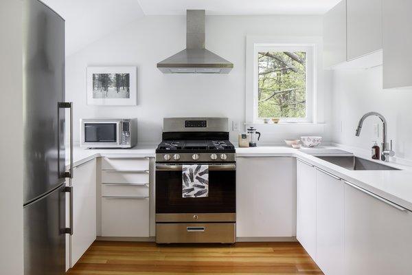Modern home with engineered quartz counter, medium hardwood floor, refrigerator, range, white cabinet, range hood, microwave, dishwasher, drop in sink, windows, casement window type, and vinyl. Photo 9 of The Bracy House