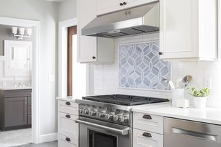 Boeing Castle in Seattle's Blue Ridge Neighborhood Taken to New Heights - Photo 2 of 4 - A custom backsplash was designed using Ann Sacks tile which compliments the marble countertop and accentuates the Wolf range.