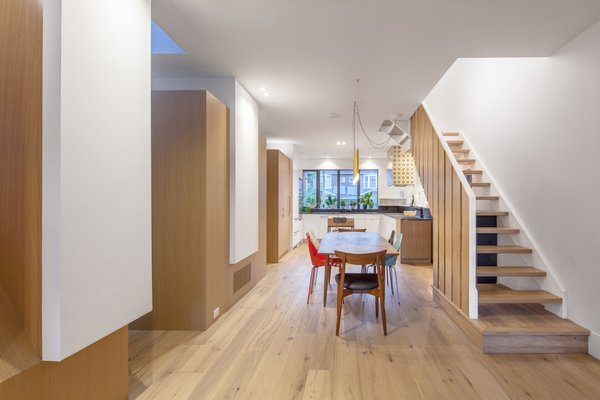 Dining area and kitchen beyond.  Service pods on the left create distinction between areas along the open plan