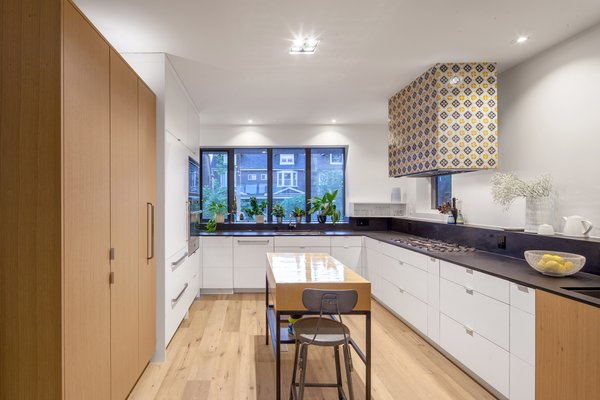 Kitchen with custom floating tiled hood vent