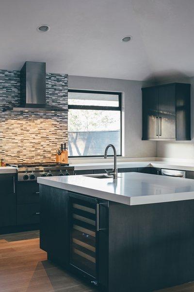 Modern home with kitchen, concrete counter, medium hardwood floor, recessed lighting, glass tile backsplashe, undermount sink, and wine cooler. Photo 4 of Crestline