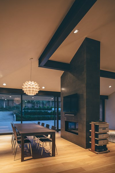 Modern home with dining room, chair, medium hardwood floor, table, pendant lighting, two-sided fireplace, and gas burning fireplace. Photo 5 of Crestline