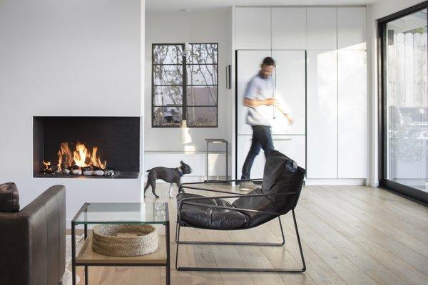 Modern home with living room, sofa, corner fireplace, and chair. Photo  of Vista De la Cumbra